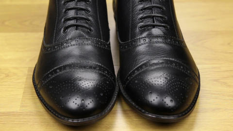 Approaching, pair of black classic men's shoes standing on a wooden floor. Men's Footage