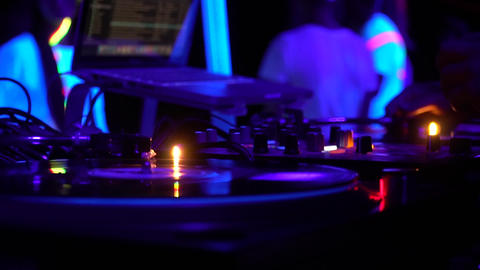 Close up of the DJ equipment, and DJ operating it, purple lighting Live Action