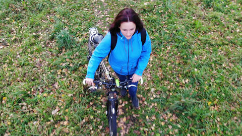 fly over woman with bicycle walking in autumn park, carefree and happy Live Action