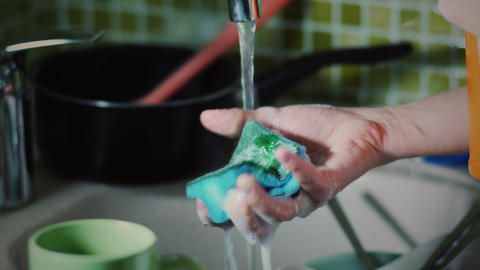 Woman washing dishes with a sponge Footage