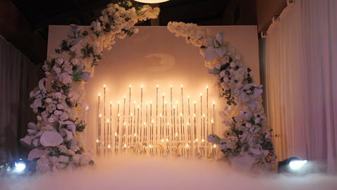 Illuminated wedding flower arch before the wedding night ceremony. Floral decor Live Action