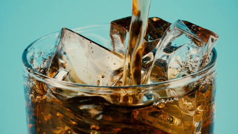 Pouring cola or brown soft drink into a glass full of ice cubes against cyan Footage