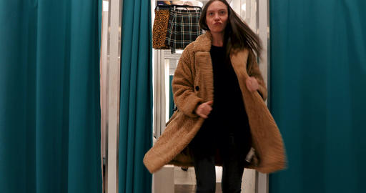 Woman dancing in a dressing room of a store in coat Live Action