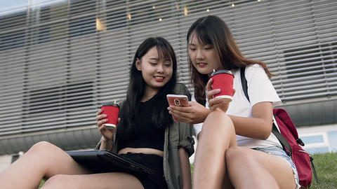 Attractive happy smiling asian girls holding in hands coffee and looking at the Footage