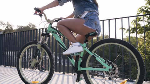 Back view of attractive young woman in stylish jeans clothes riding on bike with Footage