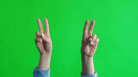 Green screen studio. Two hands show a gesture of peace Live Action