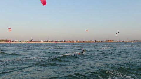 Woman with red kite is kitesurfing in the sea near the beach, recreation Live Action