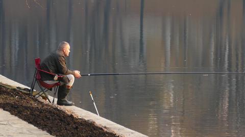 Elderly fisherman on the pond Live Action