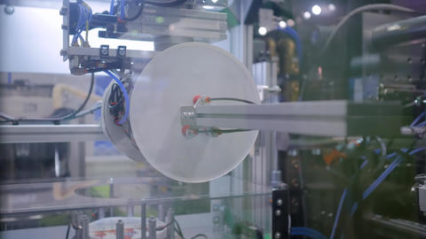 Automatic robotic arm manipulator with suction cups moves plastic lids, covers Footage