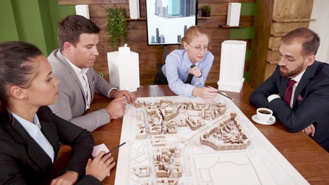 Female architect explaning her real estate project to young investors Live Action