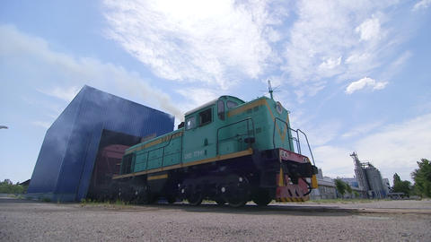 Diesel locomotive with cars in a repair depot Live Action
