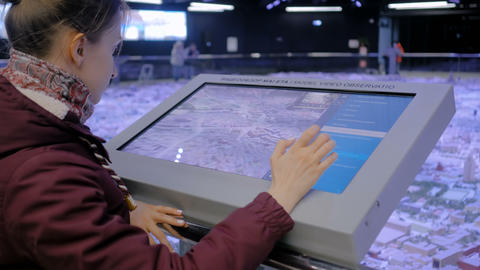 Woman using interactive touchscreen display at modern museum or exhibition Footage