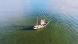 Sailing retro cargo ship moving in ocean sea calm water. Aerial flight 4k video Footage