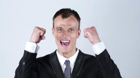 A young male executive businessman arms raised celebrating cheering shouting Footage