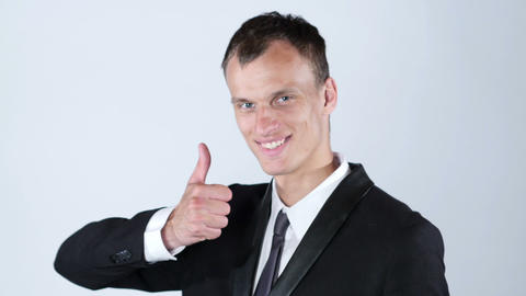 Happy businessman giving thumbs up to camera in studio Footage