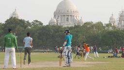 Boys play cricket on Maidan with Victoria Memorial,Kolkata,India Footage