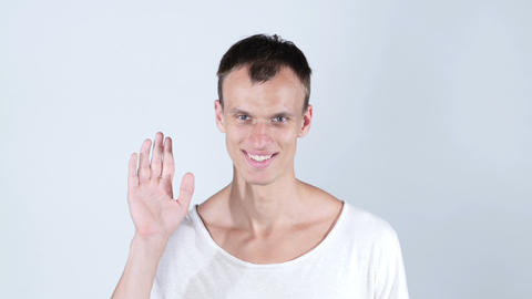 portrait of smiling man standing and showing hand sign of hi and bye bye Footage