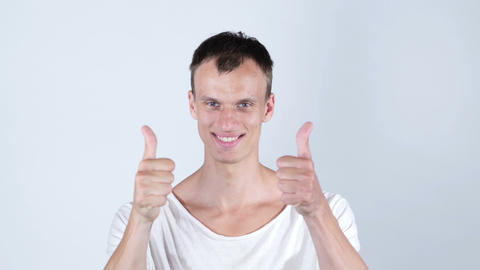Excited man laughing holding his both thumbs up , isolated on white Footage