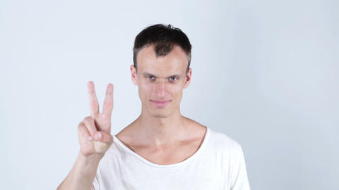 Portrait of young man smiling and showing you victory sign on white background Footage