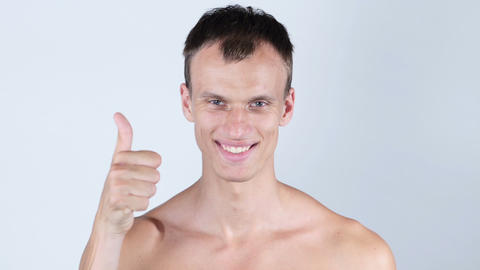 Portrait of smiling young topless man with thumb up Footage