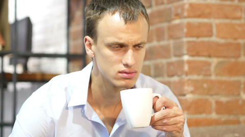 young attractive man drinking a coffee in creative work space Footage