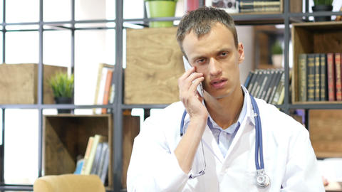 Handsome mature medical doctor consulting with patient on smartphone Footage