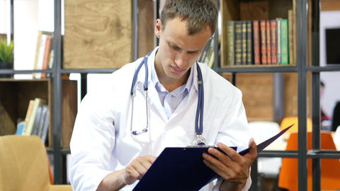 Handsome young positive doctor studies medical report in his clinic Footage