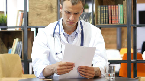 Medical office - male doctor looking down reading documents thinking Footage