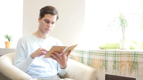 Young man is sitting on a sofa and reading a book Footage