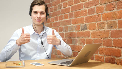 Young modern businessman excited with his success giving thumbs up ,call center Footage