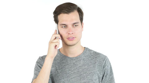 portrait of a casual young man speaking on the phone. white background Footage