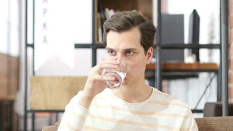 Young man drinking water sitting on a couch at home and looking at camera Footage