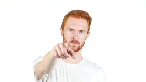 Smiling redhair young man pointing finger at camera , white background Footage