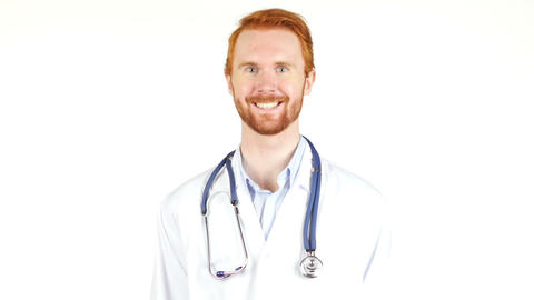 Doctor with stethoscope around his neck looking at the camera smiling, portrait Footage