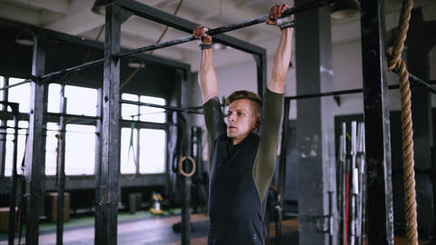 Raising feet up to bar on gym bar, attractive muscle man exercise and train in Live Action