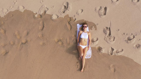 Beautiful woman relaxes on a sandy beach at the ocean Footage