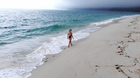 Beautiful woman on an empty beach in paradise Footage