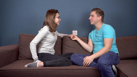 A young woman shows a positive pregnancy test to a young husband. The man is not Live Action