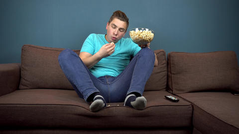 A young man is watching TV and eating popcorn. The guy is eating fallen popcorn Footage