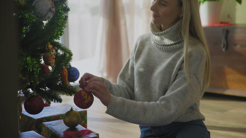 Young woman in sweater and blue jeans sitting on floor and decorate Christmas GIF