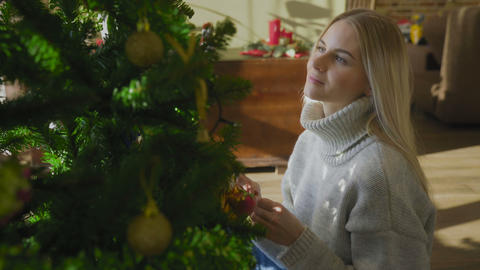 Close up of cute woman decorating Christmas tree at home GIF