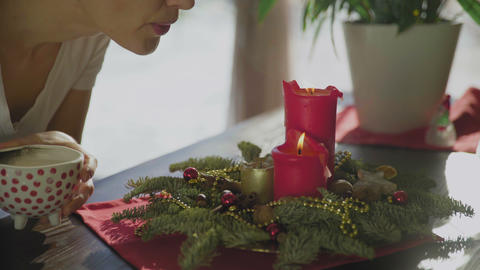 Young woman blow out Christmas candles. Classic New Year or christmas decorates GIF