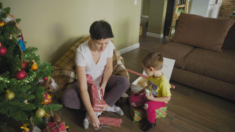 Mom and son are packing presents together. Happy family, activity with a child GIF