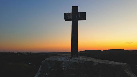 Stone cross on top of a mountain against a sunset. Cross on a sunset background Live Action