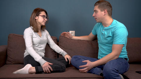 A young man shouts at a young woman. Sitting on the couch against each other Live Action
