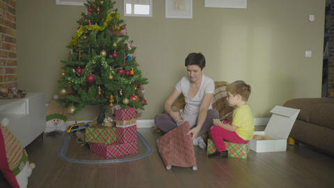 Woman and child wrapping Christmas handmade present in paper GIF