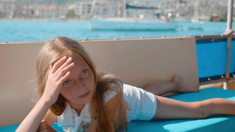 Happy girl lying on sailing yacht at sea cruise. Young teenager girl relaxing on Footage