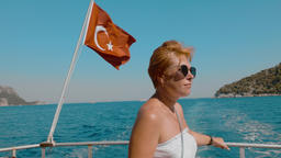 Tourist woman traveling on sea boat on turkish flag background. Happy woman Footage