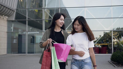 Lovely smiling asian women walking near big shopping mall and showing each other Live Action