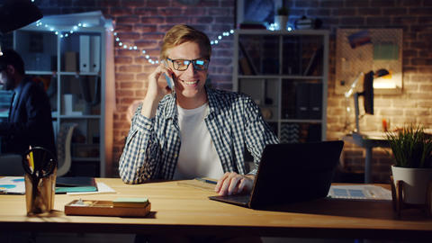 Cheerful office worker speaking on mobile phone and using laptop in dark office Footage